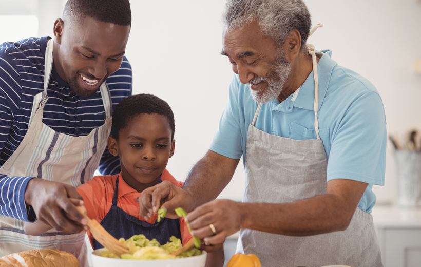 A son cooking in the kitchen together with his father and grandfather.