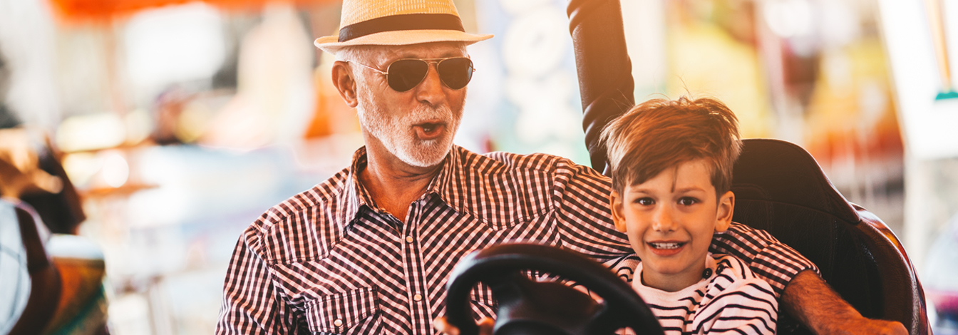 Grandfather and his son riding together in bumper cars.
